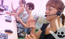 Trzy kobiety w słuchawkach na uszach migają do komputerów.